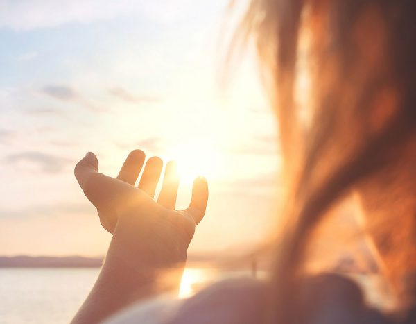 Image of woman holding her hand up to the sun.