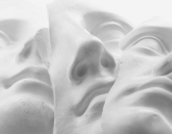 Close up image of three clay masks.